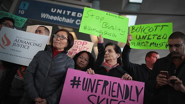 Angry protestors hold signs condemning the actions of United