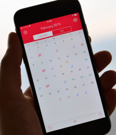 An iPhone displays a calendar that is used to schedule shifts on the Shift app.